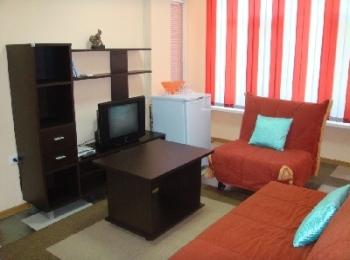 Милая комната в отеле Бавария с оранжевыми диваном и креслом