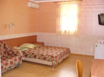 Аккуратный бежево-розовый номер с двухспальной кроватью, диваном и другими удобствами