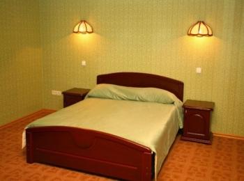 Салатовый номер с двухспальной кроватью, бра и тумбами