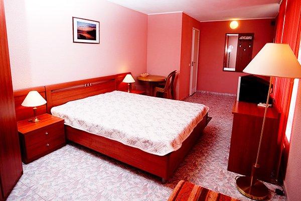 Комната типа люкс с красно-розовым интерьером и двухспальной кроватью