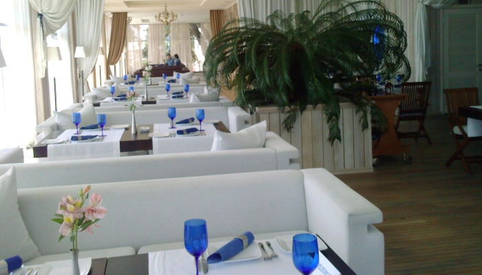 В зале есть большие живые цветы и синие бокалы