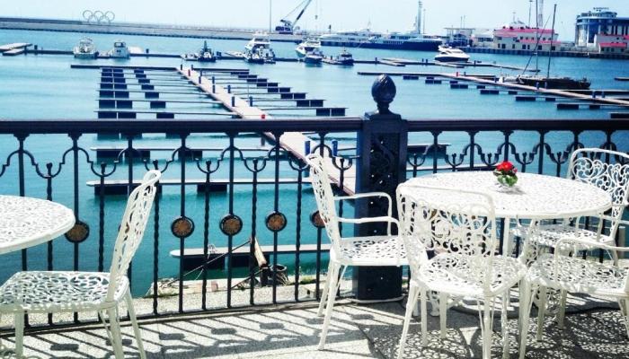С террасы в ресторане, обустроенной ажурными столами со стульями, открывается вид на море