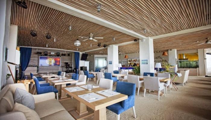 В зале ресторана Санремо в Сочи деревянные столы и мягкие синие кресла