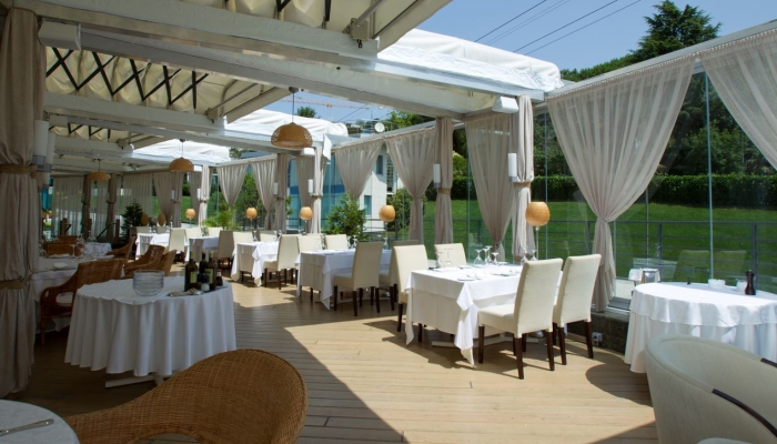 Терраса в ресторане с белыми шторками и мебелью