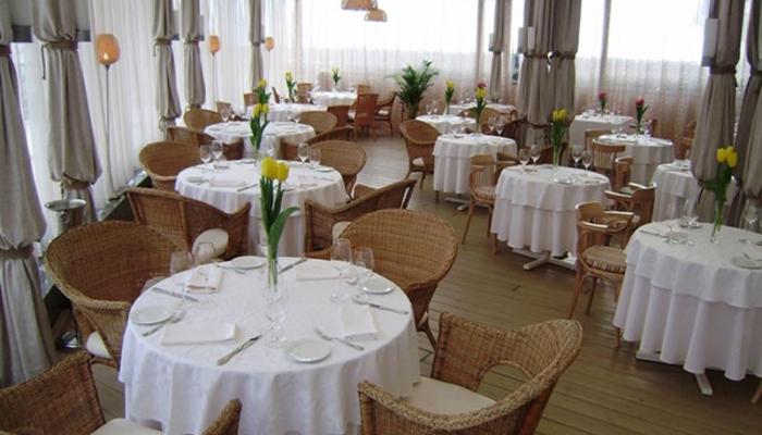 Внутренний зал с плетеными креслами и высокими вазами на столах