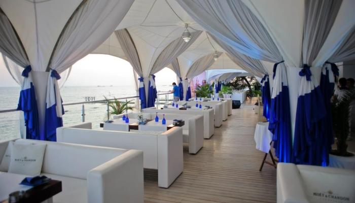 Терраса ресторана обустроена белой мебелью с синим декором